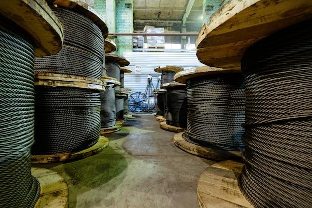 Grandes bobines de câble stockées dans les locaux de l'usine. atelier de fabrication d'élingues de câbles.