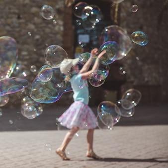 De grandes bulles de savon volent dans l'air extérieur. fille jouant en arrière-plan dans la journée d'été