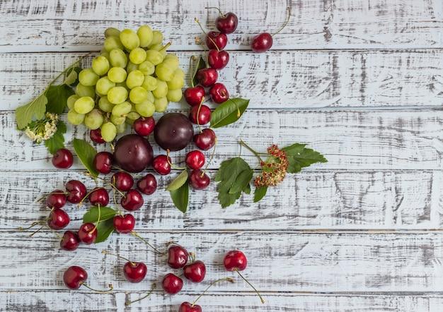Grandes cerises juteuses, prunes et raisins, feuillage et fleurs sur un fond en bois
