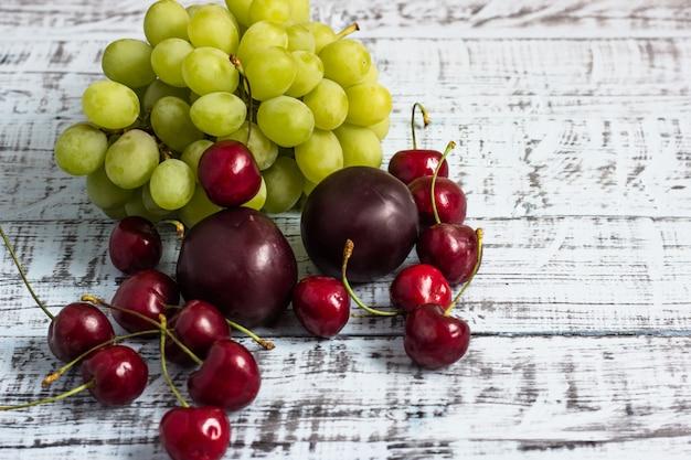 Grandes cerises juteuses, prunes et raisins sur un fond en bois, concept de l'alimentation saine