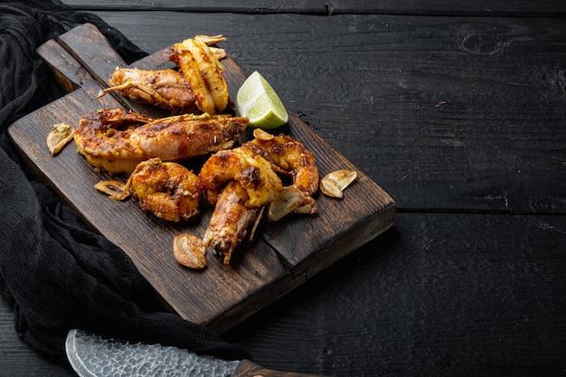 Grandes crevettes barbecue grillées avec sauce à la mangue douce et curry, sur planche de bois, sur table en bois noir