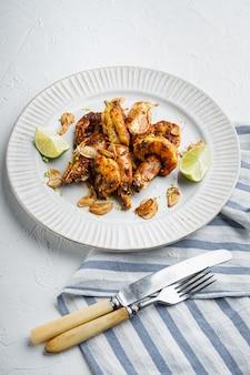 Grandes crevettes barbecue grillées avec sauce à la mangue sucrée et curry, sur assiette, sur blanc