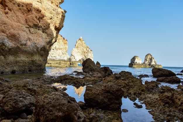 De grandes falaises qui sortent de l'eau pendant la journée à lagos, portugal