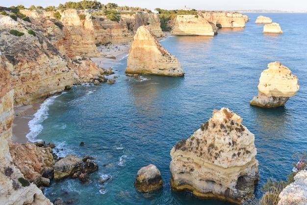 De grandes falaises qui sortent de l'eau pendant la journée