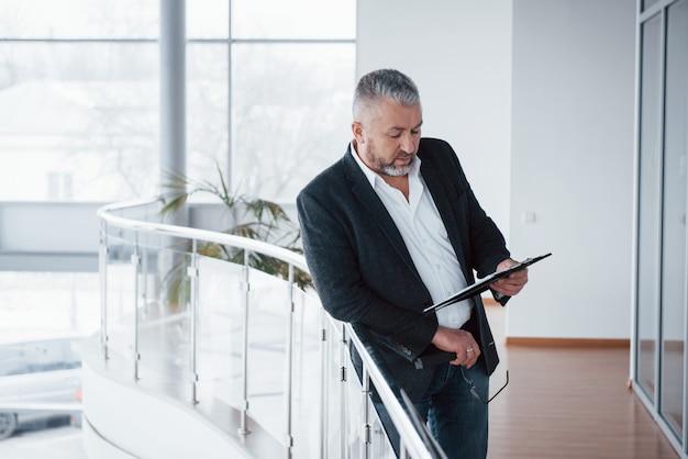 Les grandes fenêtres offrent un excellent éclairage. photo d'homme d'affaires senior dans la chambre spacieuse avec des plantes derrière. tenir et lire des documents