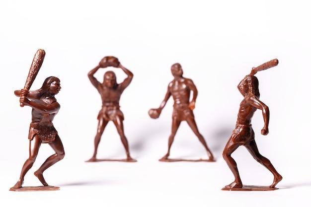 Grandes figures de jouets de peuples primitifs sur fond blanc.