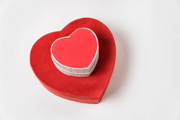 Grandes et petites boîtes en forme de coeur rouge sur table. vue de dessus. cadeaux pour la saint valentin