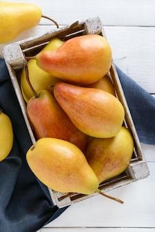 Grandes poires jaunes juteuses dans une boîte de fruits en bois rustique sur un tableau blanc