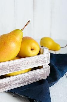 Grandes poires jaunes juteuses dans une boîte à fruits en bois rustique