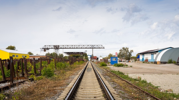 Grandes voies de chemin de fer contre le chantier de construction, atelier de production, entrepôt, grue à portique.