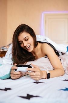 Grandhomme allongé dans son lit et jouer à un jeu vidéo, tenant le contrôleur
