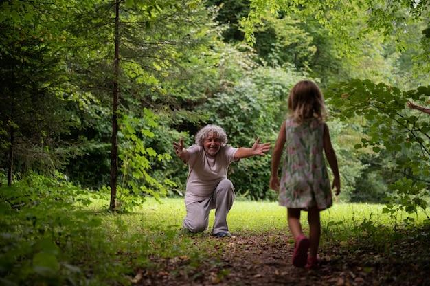 Grandpda s'agenouillant au bord d'un beau pré vert pour saluer sa petite-fille à bras ouverts.