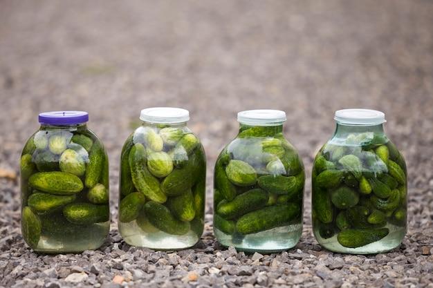 Grands bocaux en verre avec des concombres de cornichons frais et salés à la marinade