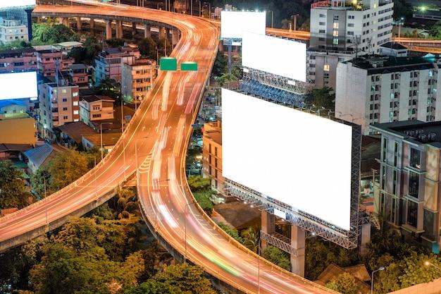 Grands panneaux d'affichage vides avec circulation sur route surélevée