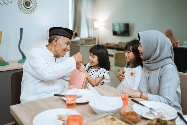 Grands-parents asiatiques donnant un cadeau aux petits-enfants lors de la célébration de l'aïd mubarak à la maison