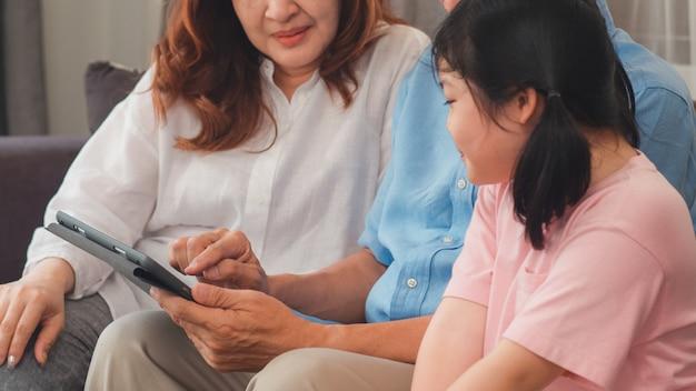 Grands-parents asiatiques et petite-fille utilisant une tablette à la maison. senior chinois, grand-père et grand-mère heureuse passent du temps en famille se détendre avec une jeune fille en vérifiant les médias sociaux, allongé sur un canapé dans le concept de salon