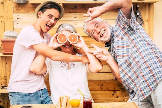 Grands-parents de couples aînés avec le neveu d'adolescent s'amusant au petit déjeuner. la folie et les rires. bois sur fond et sur table. trois personnes profitant de la vie. nourriture et boisson