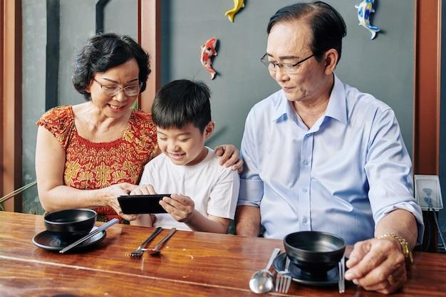 Grands-parents avec enfant à table de café