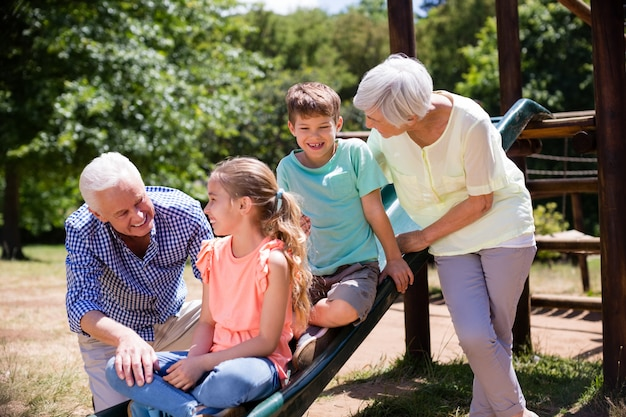 Grands-parents jouant avec leurs petits-enfants dans le parc