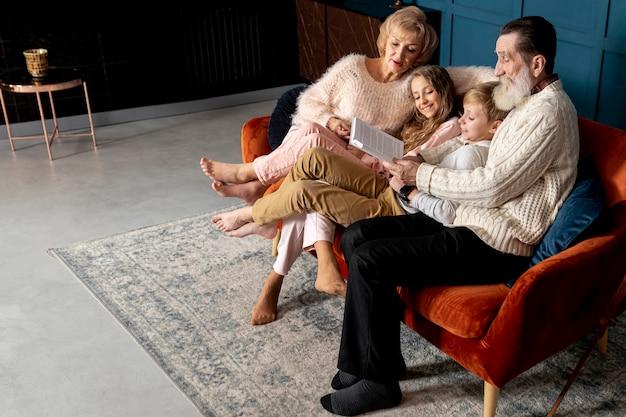 Grands-parents lisant un livre avec leurs petits-enfants avec copie espace