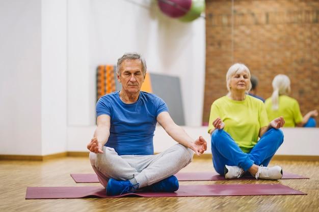 Grands-parents méditant dans la salle de gym