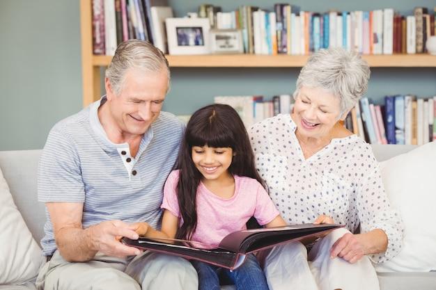 Les grands-parents montrant un album à leur petite-fille à la maison