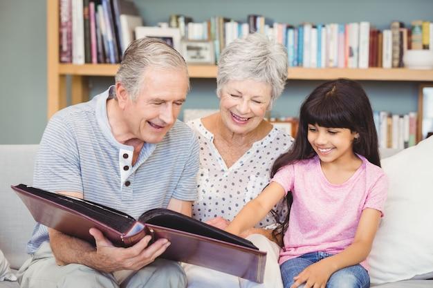 Les grands-parents montrant l'album à leur petite-fille