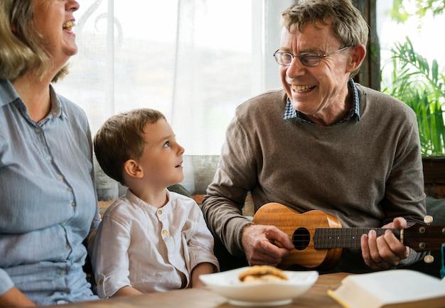 Grands-parents avec petit-fils s'amusant avec ukelele