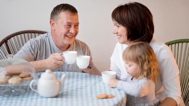 Grands-parents et petite-fille déjeunant ensemble