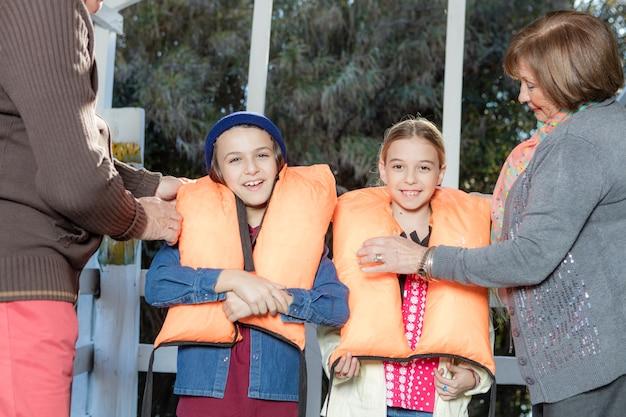 Les grands-parents petits-enfants aidant avec les gilets de sauvetage