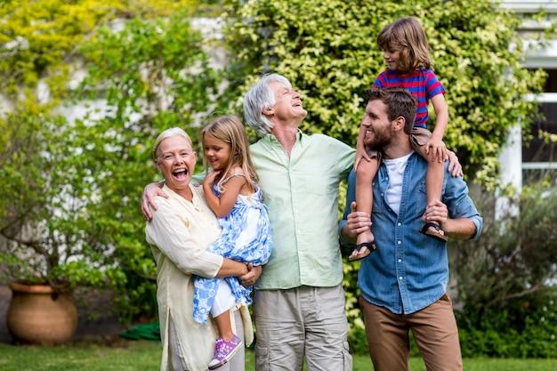 Grands-parents avec petits-enfants et fils debout dans la cour