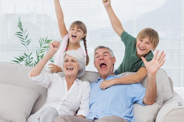 Grands-parents et petits-enfants en train de lever les bras