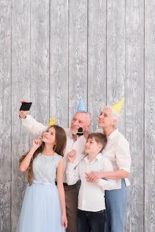 Grands-parents portant un chapeau de fête prenant un selfie sur un téléphone portable avec leurs petits-enfants tenant des accessoires en papier