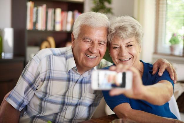 Grands-parents prenant un selfie avec leur smartphone
