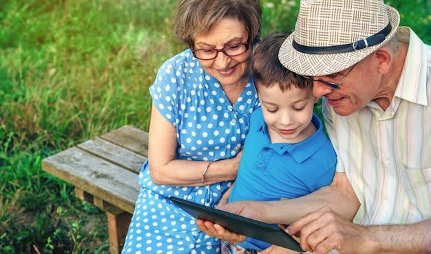 Grands-parents utilisant la tablette avec leur petit-fils assis sur un banc à l'extérieur