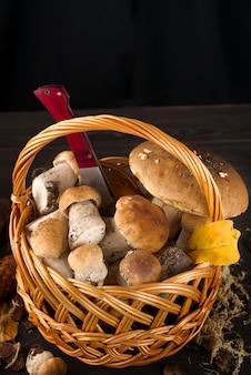 Grands et petits champignons forestiers dans un panier en bois sur fond sombre nourriture végétarienne
