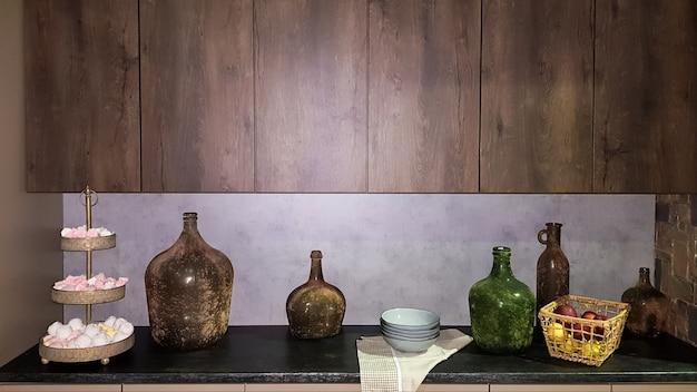 Grands vases en verre, panier de pommes et assiettes à l'intérieur d'une cuisine moderne. la combinaison du bois et du béton dans la conception. cuisine salle à manger de style moderne.