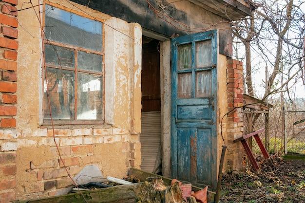 Grange en brique abandonnée de style rétro ou ferme avec portes bleues ouvertes et grande fenêtre dans le village,