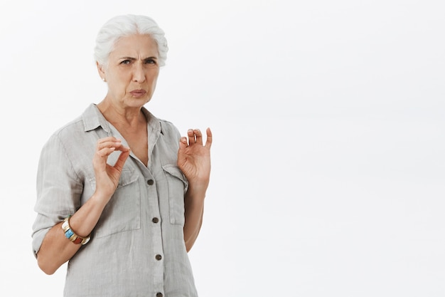 Granny pointilleux dégoûté grimaçant et regardant avec aversion