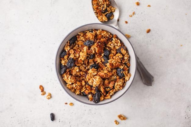 Granola au four avec des raisins secs dans un bol, fond blanc.