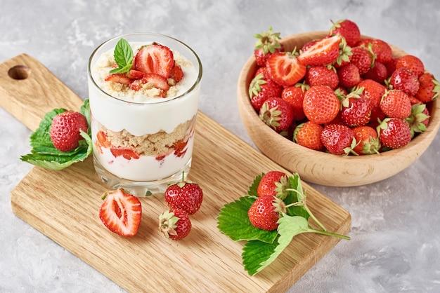 Granola aux fraises ou smoothie dans un verre et des baies fraîches dans un bol en bois, vue de dessus. petit-déjeuner sain