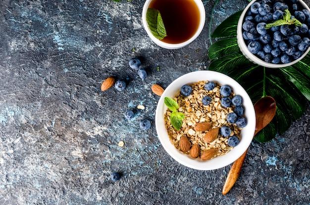 Granola aux myrtilles en assiette et tasse de thé pour le petit déjeuner