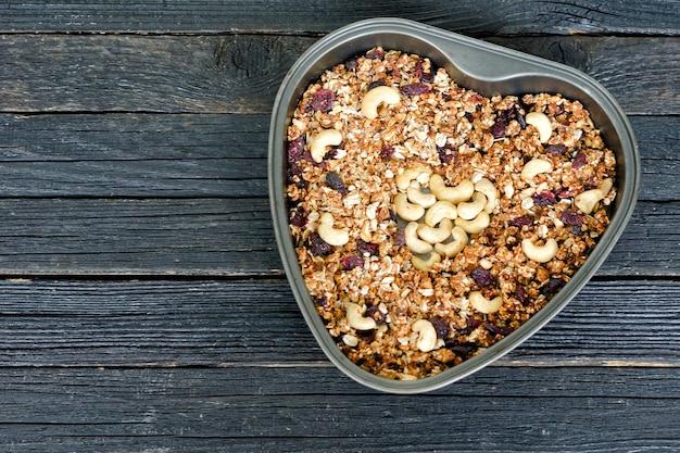 Granola aux noix de cajou dans un plat de cuisson en forme de coeur