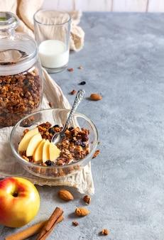 Granola aux pommes avec des épices pour le petit déjeuner sur une table grise