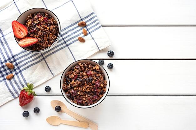Granola cuit au four dans deux bols avec des baies, des amandes, une serviette et des cuillères écologiques sur table blanche, vue du dessus