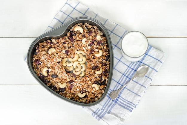 Granola dans une plaque à pâtisserie en forme de coeur, un verre de yaourt