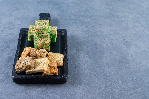 Granola et délices turcs sur une planche sur la surface en marbre