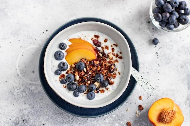 Granola avec du yogourt, des myrtilles, de la pêche et du miel