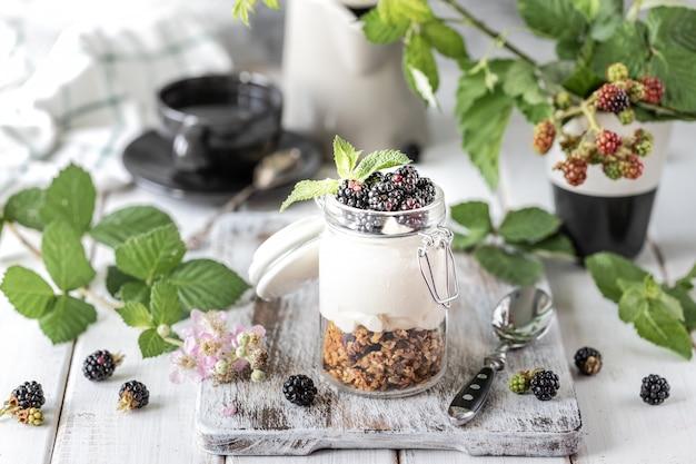 Granola fait main avec du yaourt naturel blanc avec des mûres dans un bocal en verre transparent, des fleurs et des feuilles sur un fond en bois blanc.