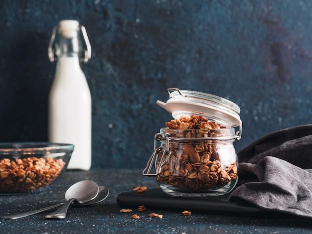 Granola fait maison dans un bocal en verre sur une table sombre